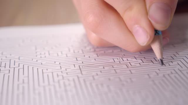 vídeos de stock, filmes e b-roll de o menino está resolvendo o labirinto impresso no papel com lápis em casa. - explicar