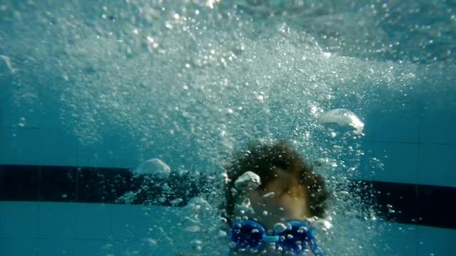 stockvideo's en b-roll-footage met boy jumping and diving in swimming pool. - swimmingpool kids