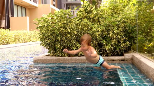 vídeos de stock e filmes b-roll de boy jumping into outdoor swimming pool in tropical resort - jump pool, swimmer