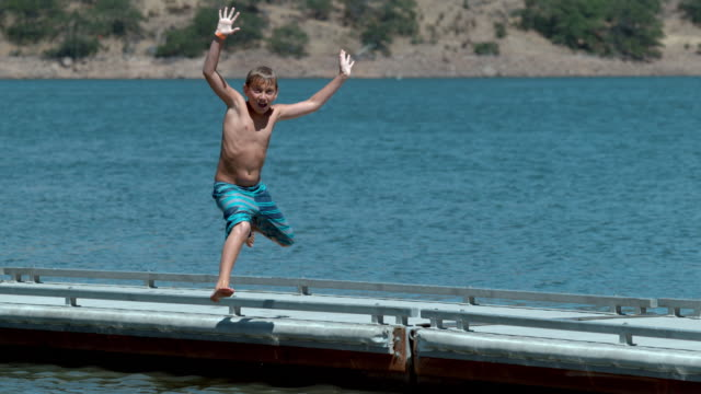 Boy jumping off dock into lake in super slow motion video