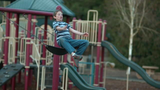 junge aus swing in zeitlupe springen - kind schaukel stock-videos und b-roll-filmmaterial