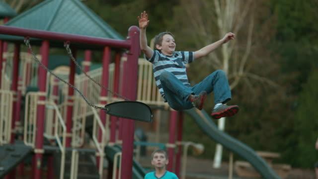 boy jumping off swing in slow motion - oscillare video stock e b–roll