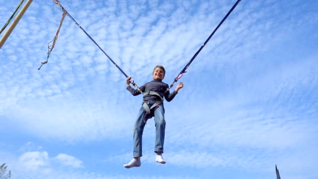 boy jumping on bungee trampoline - bungee jumping video stock e b–roll
