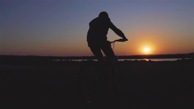 Pojke kid ridning cykel på våren nära floden vid vacker solnedgång i slow motion video