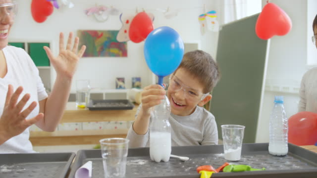 DS Boy laughing while making his balloon inflate itself in the school science experiment