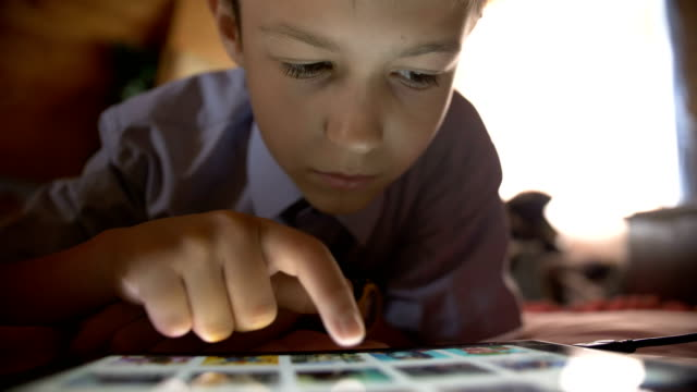 boy lays in a bed and use on a tablet pc at home - solo un bambino maschio video stock e b–roll