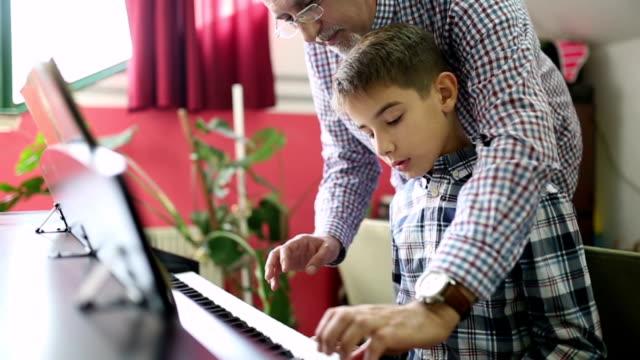 vídeos de stock e filmes b-roll de boy learning the piano with her teacher - piano