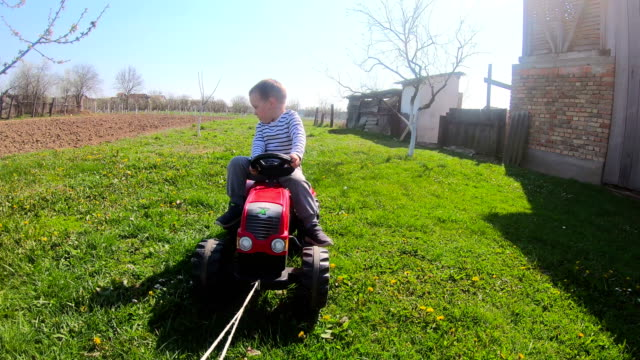 vídeos de stock e filmes b-roll de boy learning to drive tractor toy in the backyard - trator