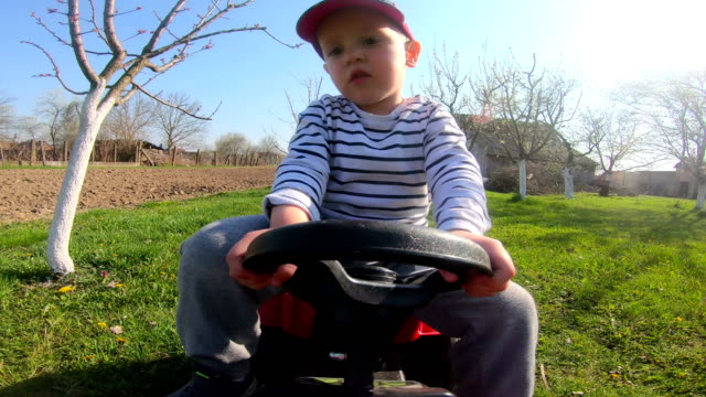 Boy Learning To Drive tractor toy in the backyard