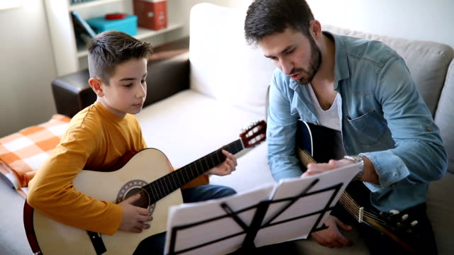 vídeos de stock e filmes b-roll de boy learning to play guitar at home - instrumental