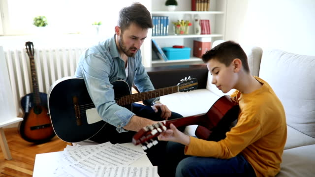 Boy learning to play guitar at home video
