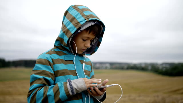 Boy listening to music from your phone, boy in a field on the mountain in the evening video