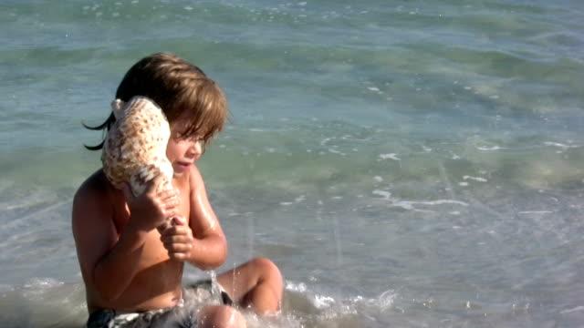 vidéos et rushes de garçon en écoutant un coquillage - coquillage