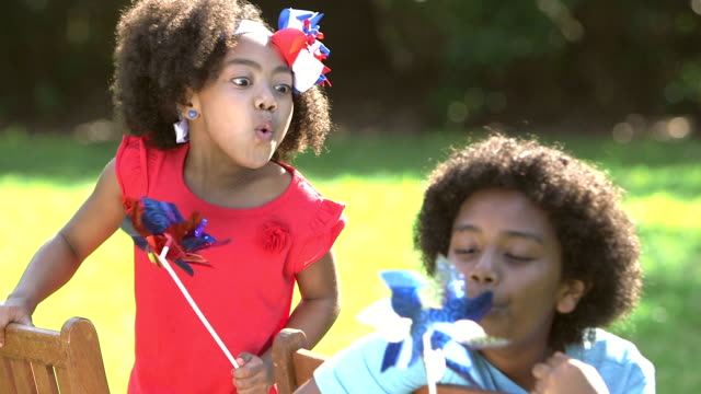 Boy, little sister playing with red, white and blue pinwheels video