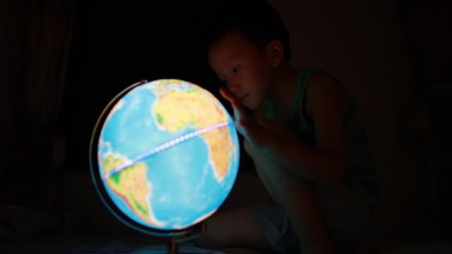 pojken tittar på globen - bordsjordglob bildbanksvideor och videomaterial från bakom kulisserna