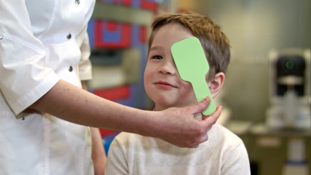 Boy looking at vision test with one eye covered with occluder video