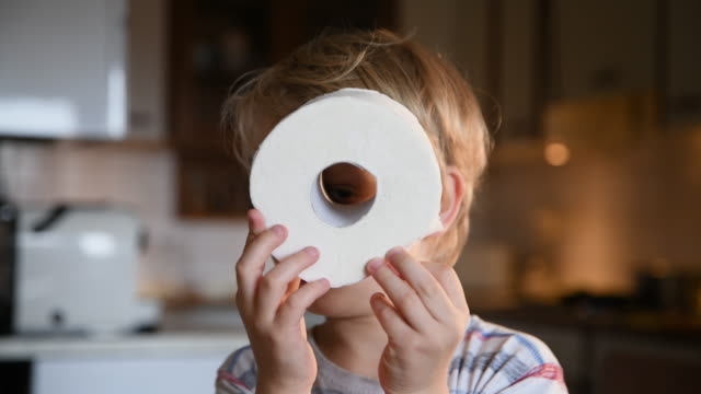 Boy looking into improvised binoculars Little boy looking into roll of toilet paper bathroom stock videos & royalty-free footage