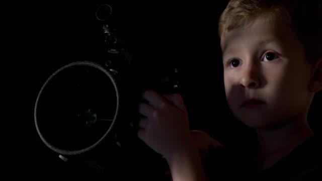 A boy looking through a astronomy telescope