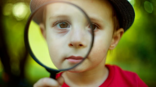 Boy looking through a magnifier Boy looking through a magnifying glass magnifying glass stock videos & royalty-free footage