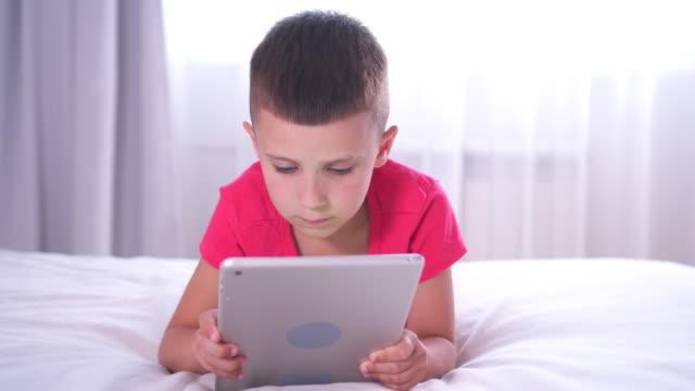 boy looks focused while using digital tablet - solo un bambino maschio video stock e b–roll