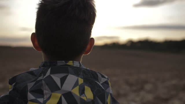 boy looks into the distance at the sky at sunset back view, close up video