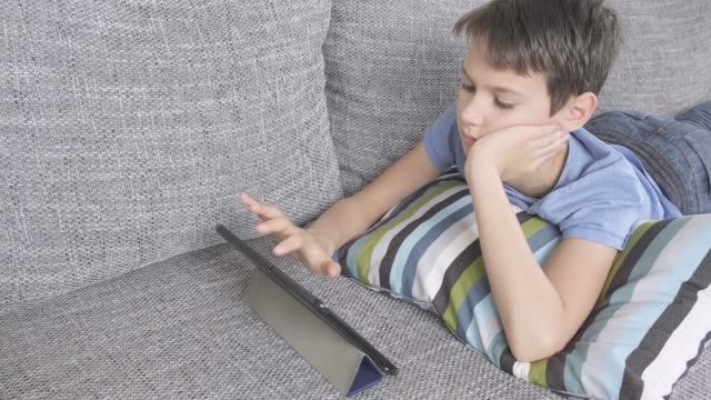 boy lying on sofa with digital tablet computer at home. technology, distance education, online learning, video call, playing games concept - solo un bambino maschio video stock e b–roll