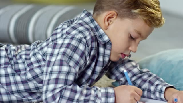 Boy Lying on the Floor and Drawing video