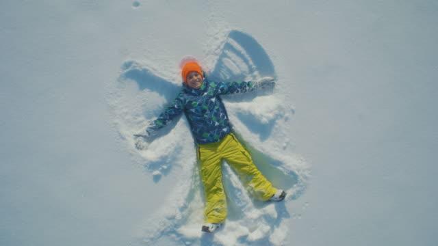 pojke gör en ängel i snön - snow kids bildbanksvideor och videomaterial från bakom kulisserna