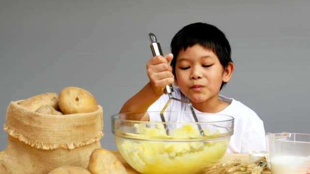 vídeos de stock e filmes b-roll de boy making mashed potato - utensílio