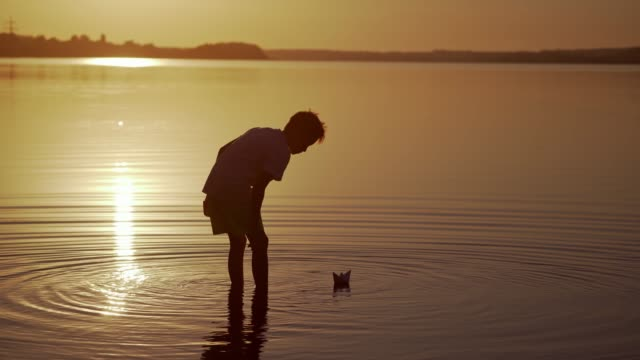 Bидео Boy near the lake at sunset.