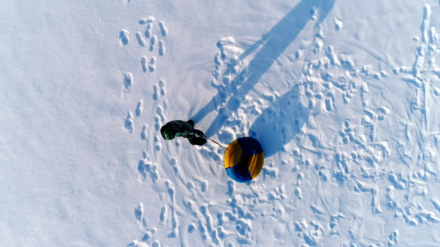 boy of 7 years is whirling with the tubing in the snow. aerial footage. - trekking sul ghiaccio video stock e b–roll