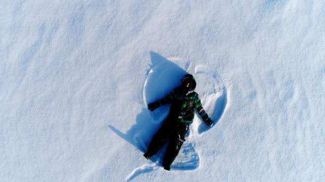 pojke på 7 år gör snöängel, aerial film - snow kids bildbanksvideor och videomaterial från bakom kulisserna