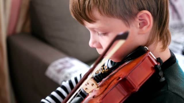 Boy of 8 years is learning to play violin.