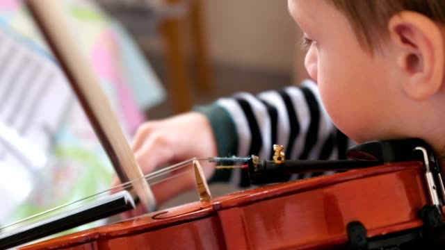Boy of 8 years is learning to play violin. video