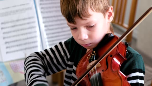 Boy of 8 years is playing violin.