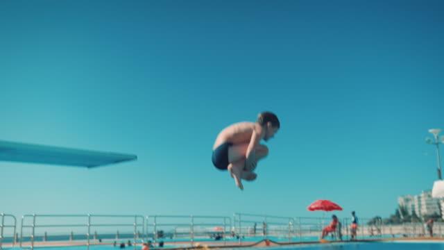 ragazzo sul trampolino per tuffi - saltare video stock e b–roll