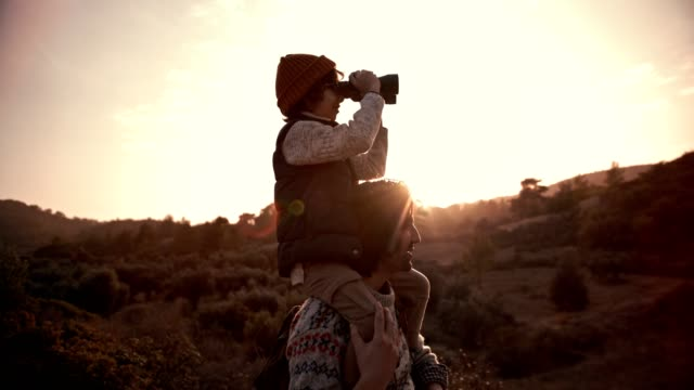 Boy on father's shoulders using binoculars and looking at view video