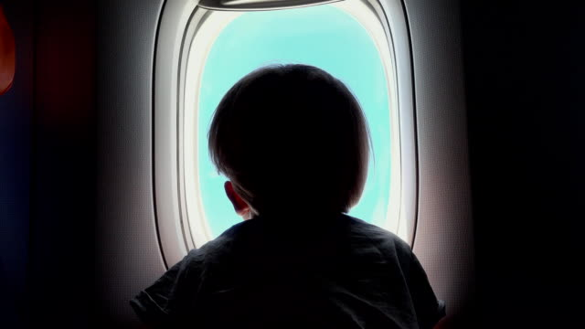 Boy on the seat looking out an airplane window