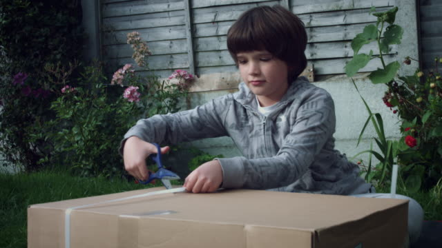 4K Boy Opening an Cardboard Box with Present video