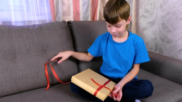 Boy opens a box of chocolate candies sitting on the couch at home. video