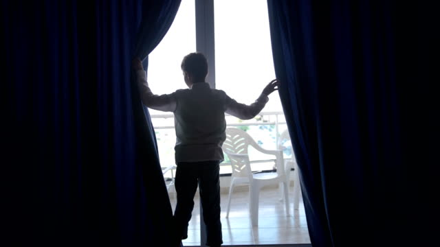 boy opens the curtains and goes to the balcony in the hotel