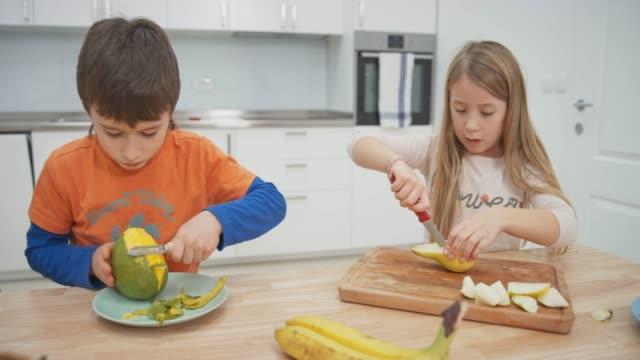 Boy peeling a mango and girl cutting a pear