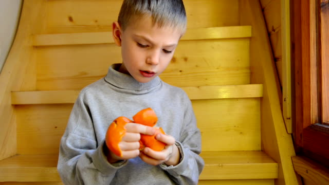 Boy peeling a tangerine video