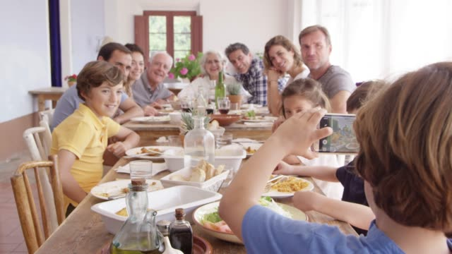 Boy Photographing Family On Phone At Dining Table Dolly shot of boy photographing multi-generational family through smart phone. Parents and children are sitting at dining table. They are enjoying lunch together at home. granddaughter stock videos & royalty-free footage
