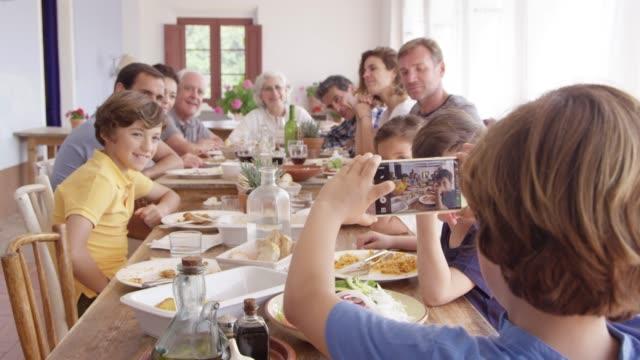 boy photographing family through phone at table - внук стоковые видео и кадры b-roll