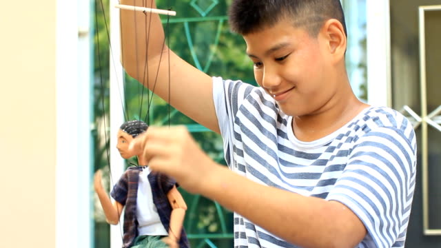 Boy playing a marionette Boy playing a marionette marionette stock videos & royalty-free footage