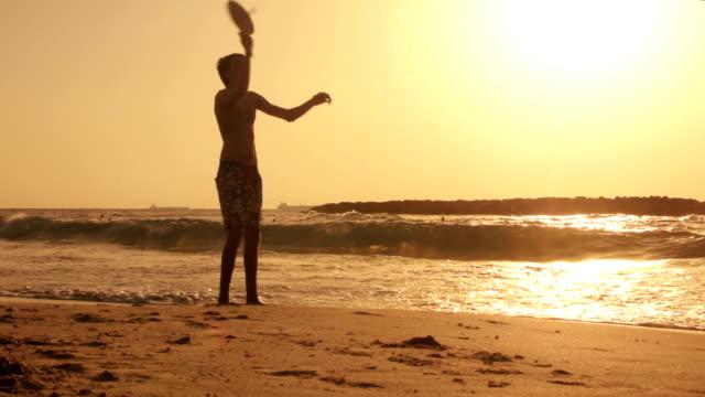 Boy playing beach tennis at sunset video
