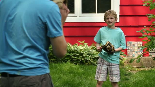 Boy playing catch in the backyard video