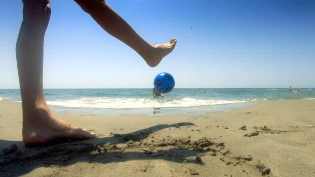 junge, der fußball spielt. strandurlaub - achtlos stock-videos und b-roll-filmmaterial