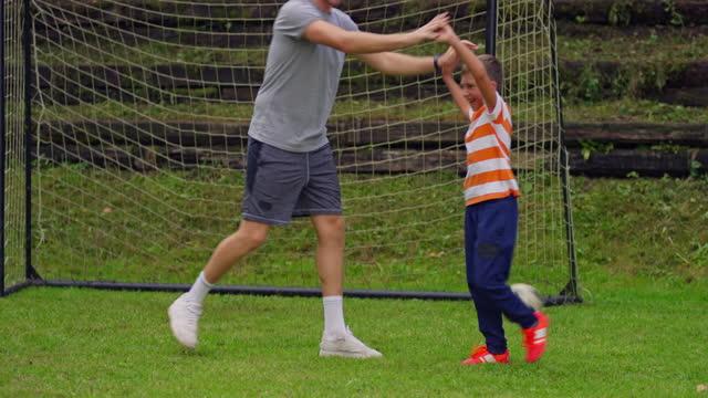 ragazzo che gioca a calcio con suo padre e un amico - padre single video stock e b–roll